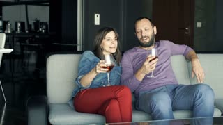 Young couple talking and drinking wine on sofa at home