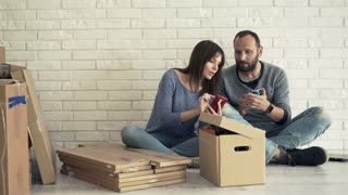 Young couple talking and using smartphone while sitting on floor at their new home
