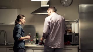 Young couple talking, kissing and drinking wine in the kitchen