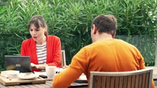 Young couple using modern laptop during breakfast on terrace at home