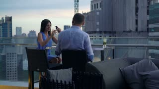 Young couple using smartphone on terrace in cafe in the city, 4K