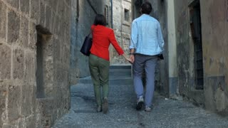 Young couple walking in the old street in the city, super slow motion