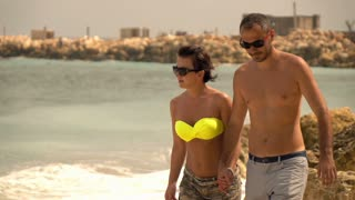 Young couple walking on beach and holding hands, super slow motion
