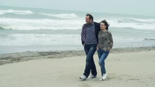 Young couple walking on beach and kissing on a stormy day, 240fps