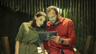 Young couple watching movie on tablet at home at night
