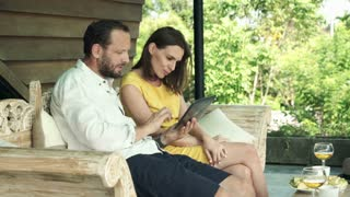 Young couple watching movie on tablet on sofa on terrace