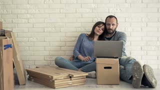 Young couple watching movie sitting on floor at their new home