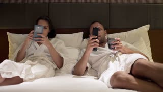 Young couple watching tv and using smartphone in bed during night