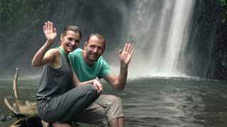 Young couple waving hand by beautiful waterfall In Bali