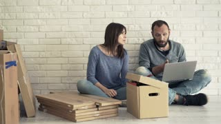 Young couple with laptop and smartphone fighting at their new home