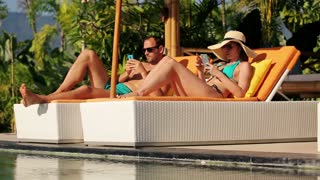 young couple with smartphone on sunbed by swimmning pool