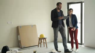Young couple with tablet computer talking about new home project