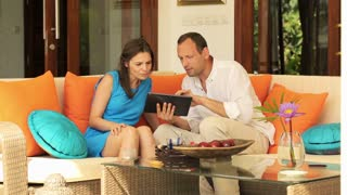 young couple with tablet on comfortable sofa at home