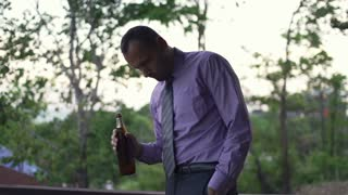 Young drunk businessman walking with beer on terrace in the evening, shot at 240fps