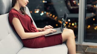 Young, elegant woman using laptop while sitting on sofa at home during night