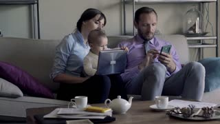 young family sitting with laptop and smartphone on sofa at home