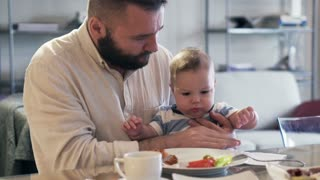 Young father eating breakfast with small son on his knee