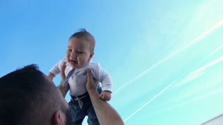Young father playing with his small, funny son against the sky, super slow motion