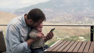 Young father showing something on smartphone his small son while sitting on terrace