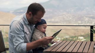 Young father showing something on tablet his small son while sitting on terrace