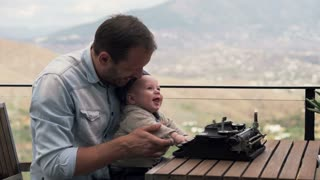 Young father showing typewriter to his small son while sitting on terrace