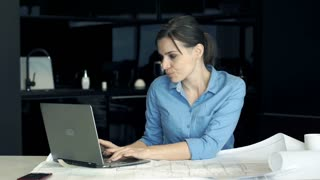 Young female architect having head pain during work on laptop by table in the kitchen