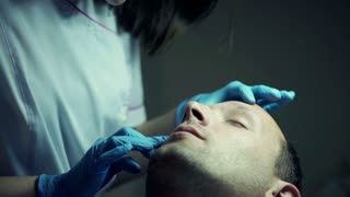Young female doctor examining man face at beauty salon