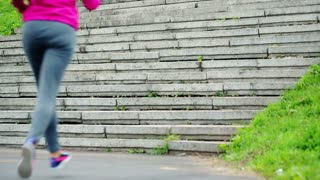 young female jogger climbing up the stairs