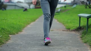 young female jogger stretching legs before jogging in the city