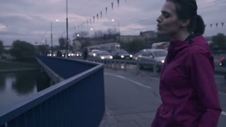 young female jogger stretching legs on the city bridge super slow motion, shot at 240fps