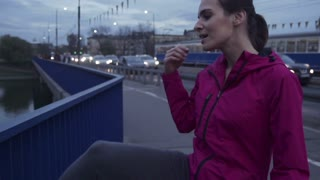 young female jogger stretching legs on the city bridge