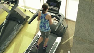 Young, fit woman running on treadmill in gym, top view, shot at 240fps
