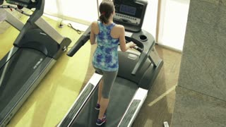 Young, fit woman running on treadmill in gym, top view.
