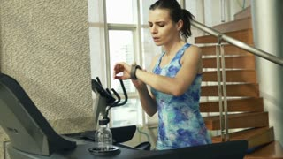 Young, fit woman with smartwatch running on treadmill in gym, top view.