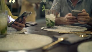 Young friends getting food from waiter while sitting with smarphone in cafe, focus on hands, 4K