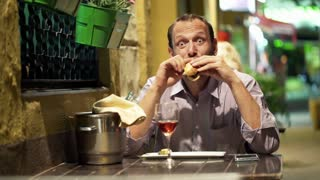 Young, funny man eating sandwich in cafe at night