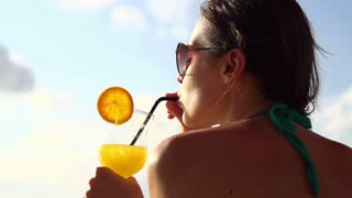 Young girl in bikini drinking cocktail, shot at 240fps