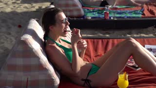 Young girl in bikini eating ice cream, shot at 240fps