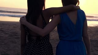 Young girlfriends admiring sunset standing on beach, super slow motion, shot at 240fps