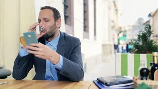 Young, handsome businessman drinking beer and using smartphone in cafe city