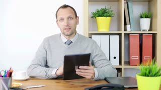 Young handsome businessman giving presentation with tablet