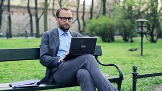 Young, handsome businessman sitting with laptop on bench in city park