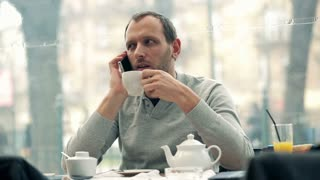 young handsome man drinking tea and talking on the cellphone in the cafe