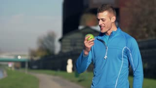 Young, handsome man eating apple in city while woman jogging