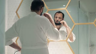 Young handsome man in bathrobe brushing his teeth in bathroom