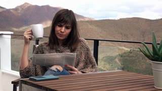 Young, handsome man in pyjama reading newspaper on terrace with mountains view, 4K