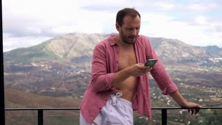 Young handsome man in pyjamas standing with smartphone on terrace with mountains view, 4K