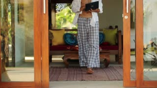 Young handsome man standing with laptop in luxury villa