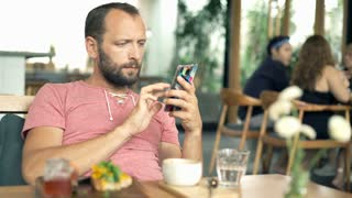 Young, handsome man texting on smartphone and drinking beverage in cafe, 4K