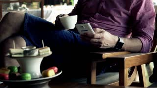 Young man using smartphone, drinking coffee in cafe. Focus on hands
